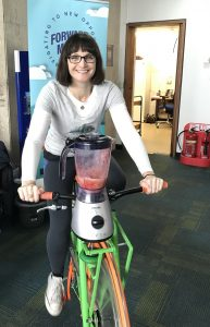 International Women's Day event attendee has a go on a smoothie bike