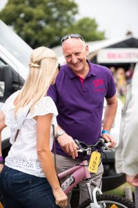 Paul Coulson speaking with a festival goer at Village Green